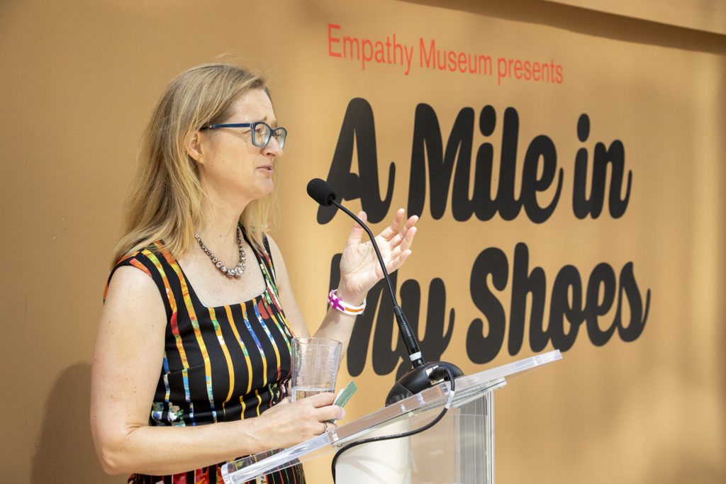"""Erin Trapp, executive director of the Biennial of the Americas, introduces the Empathy Museum's traveling """"A Mile in My Shoes"""" exhibit downtown. Aug. 8, 2019. (Kevin J. Beaty/Denverite)"""