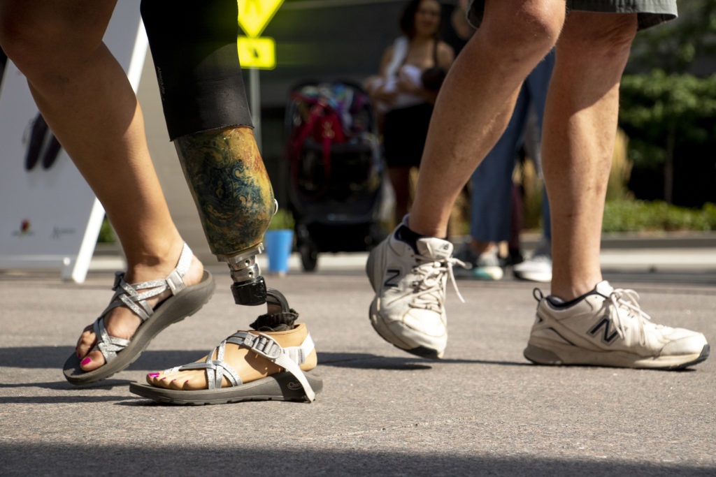 """Emily Harvey's prosthetic leg and foot and a pair of sneakers checked out from the Empathy Museum's traveling """"A Mile in My Shoes"""" exhibit, part of this year's Biennial of the Americas, Aug. 8, 2019. (Kevin J. Beaty/Denverite)"""