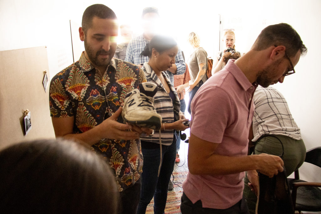"""Artist Jonathan Saiz checks out a pair of sneakers, and the story attached to them, inside the Empathy Museum's """"A Mile In My Shoes"""" exhibit brought to the 16th Street Mall by the Biennial of the Americas. Aug. 8, 2019. (Kevin J. Beaty/Denverite)"""