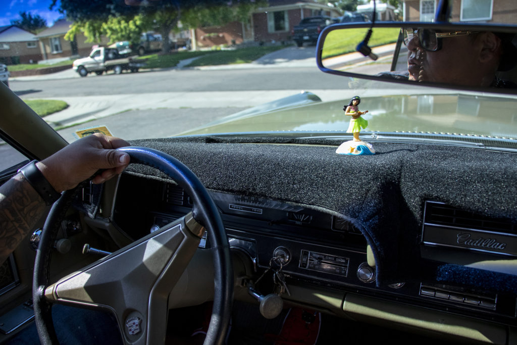 Ben Chavez gives a guy a ride in his Cadillac around the Twin Lakes block where he lived as a kid. Aug. 14, 2019. (Kevin J. Beaty/Denverite)