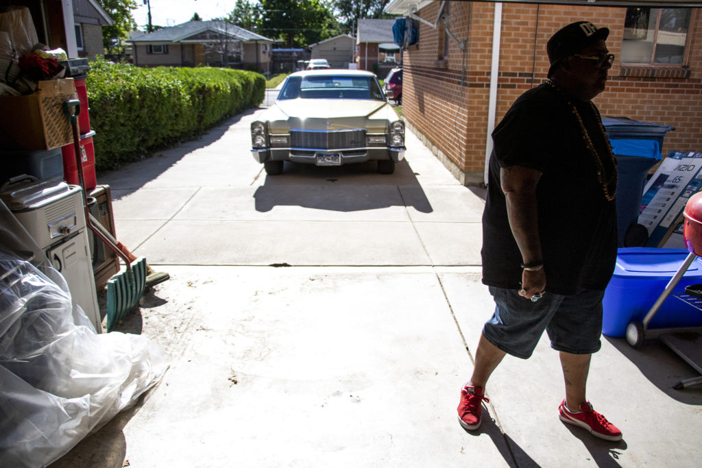 Ben Chavez shows a guy his Cadillac at the Twin Lakes home where he lived as a kid. Aug. 14, 2019. (Kevin J. Beaty/Denverite)