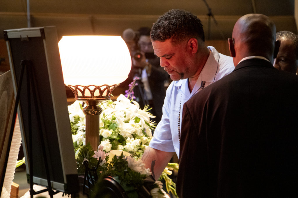 """Hasira """"Soul"""" Ashemu peers into the casket of his father, Colorado Black Panther Party founder Lauren Watson, during his funeral, Aug. 21, 2019. (Kevin J. Beaty/Denverite)"""