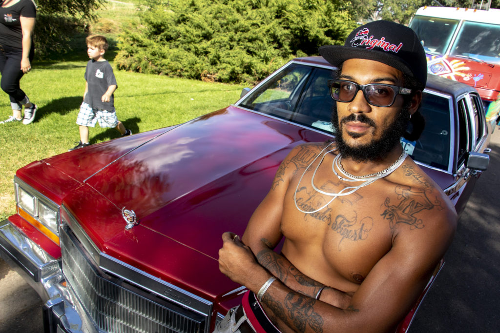 Jerry Crawford III poses with his low rider at Barnum Park after a cruise down Federal Boulevard. Aug. 25, 2019. (Kevin J. Beaty/Denverite)