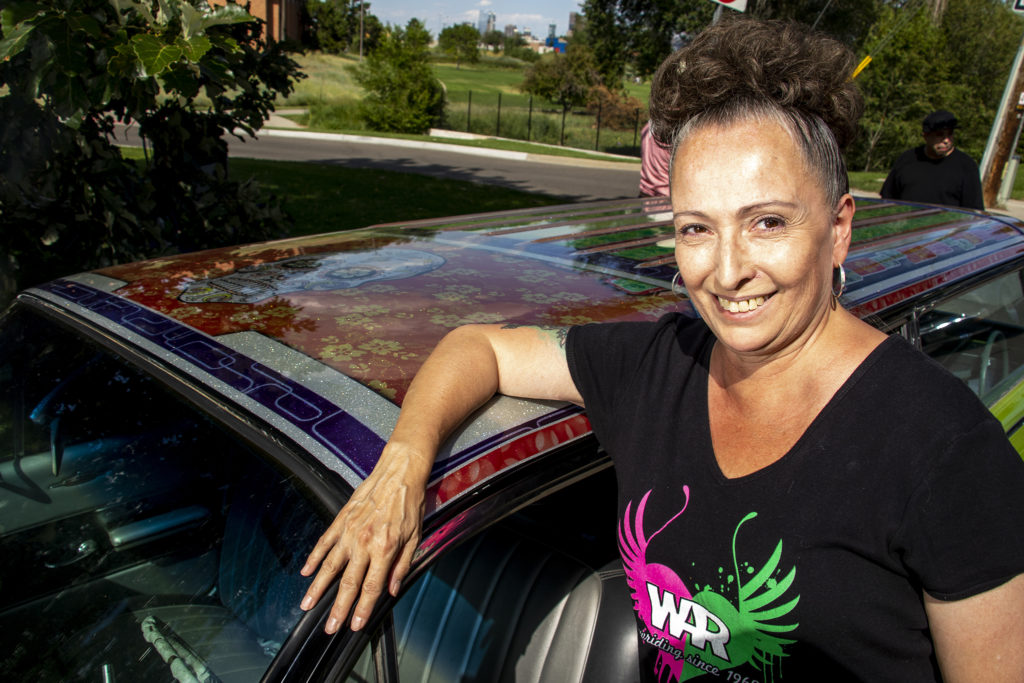 Marlene Swazo poses with the car her husband built for her at Barnum Park, after a cruise down Federal Boulevard. Aug. 25, 2019. (Kevin J. Beaty/Denverite)
