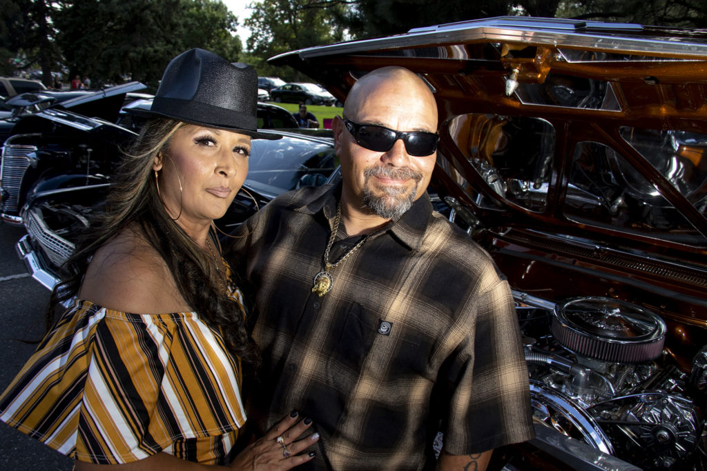 George and Angelina Gutierrez pose for a photo with their low rider at Barnum Park after a cruise down Federal Boulevard. Aug. 25, 2019. (Kevin J. Beaty/Denverite)