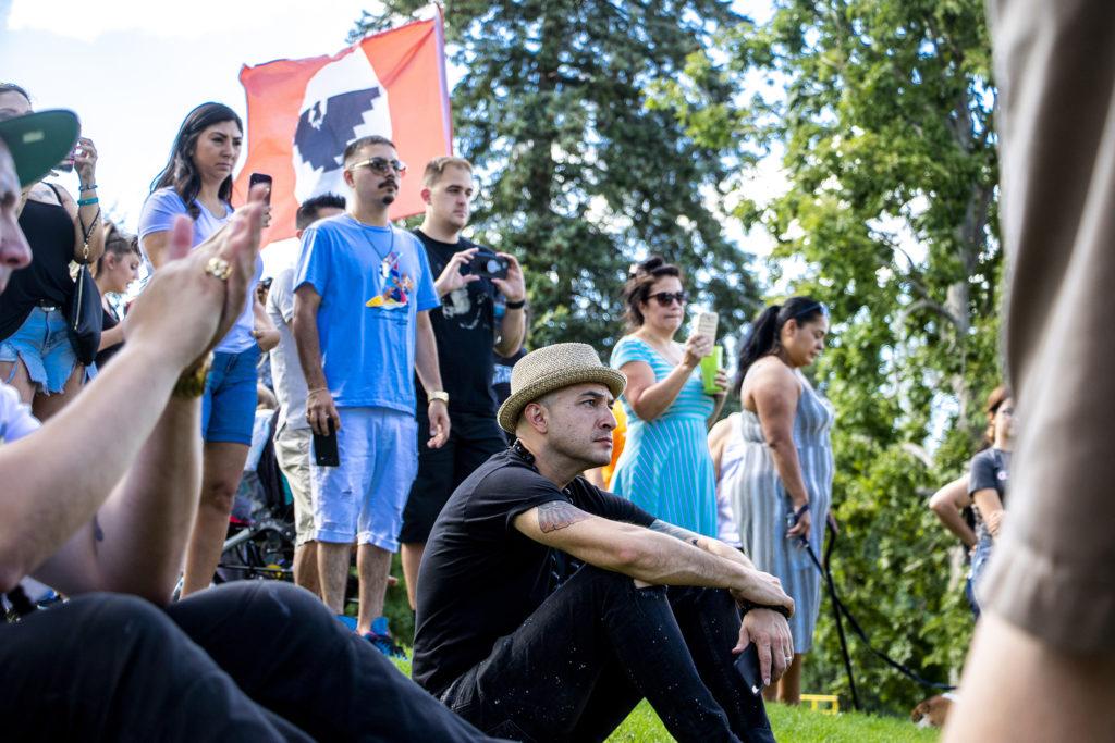 Colorado Poet Laureate Bobby LeFebre listens to Denver Police Chief Paul Pazen speak at Barnum Park after a cruise down Federal Boulevard. Aug. 25, 2019. (Kevin J. Beaty/Denverite)