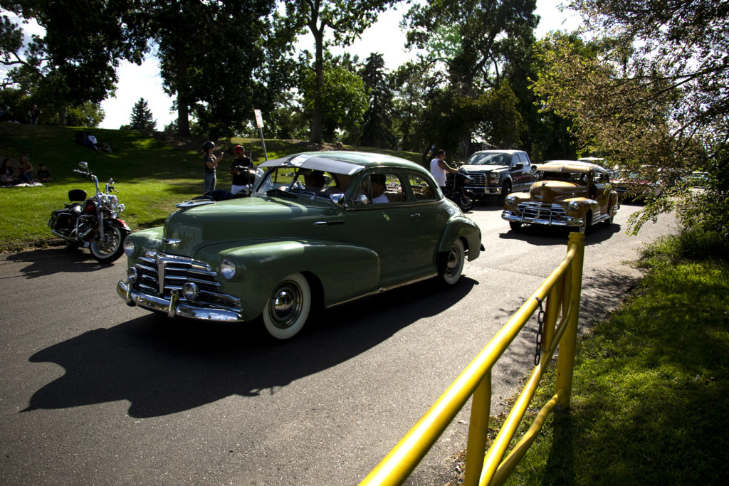 Cars drive through Barnum Park after a cruise down Federal Boulevard. Aug. 25, 2019. (Kevin J. Beaty/Denverite)