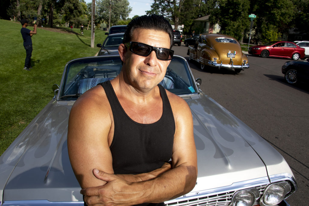 Officer Mark Garcia poses for a portrait with his low rifer at Barnum Park after a cruise down Federal Boulevard. Aug. 25, 2019. (Kevin J. Beaty/Denverite)