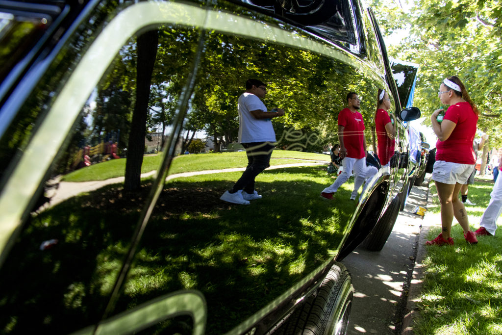 Donna Miramontes checks out a shiny low rider parked by La Raza (or Columbus) Park before a cruise down Federal Boulevard. Aug. 25, 2019. (Kevin J. Beaty/Denverite)