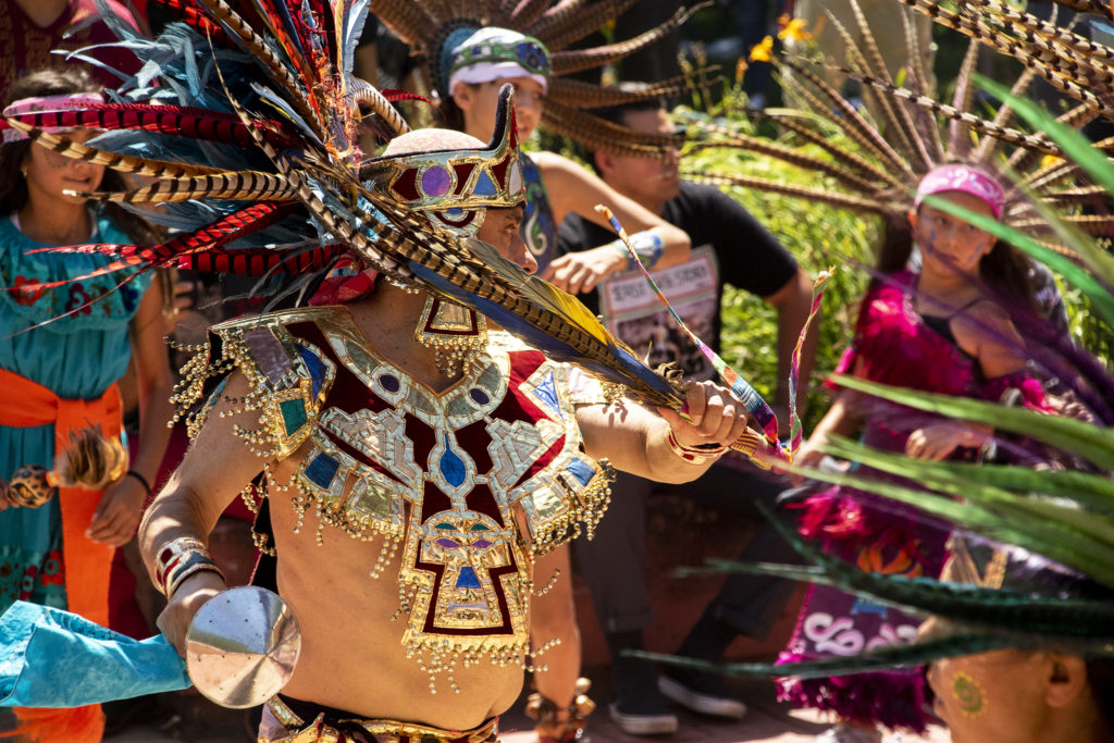 Aztec dancers perform a ceremonial dance at La Raza (or Columbus) Park before a cruise down Federal Boulevard. Aug. 25, 2019. (Kevin J. Beaty/Denverite)