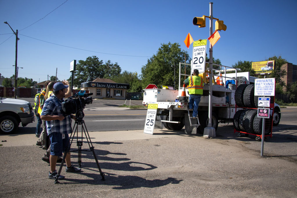 Denver Public Works replaces a speed limit sign, with a lower limit, on Evans Avenue. Aug. 30, 2019. (Kevin J. Beaty/Denverite)