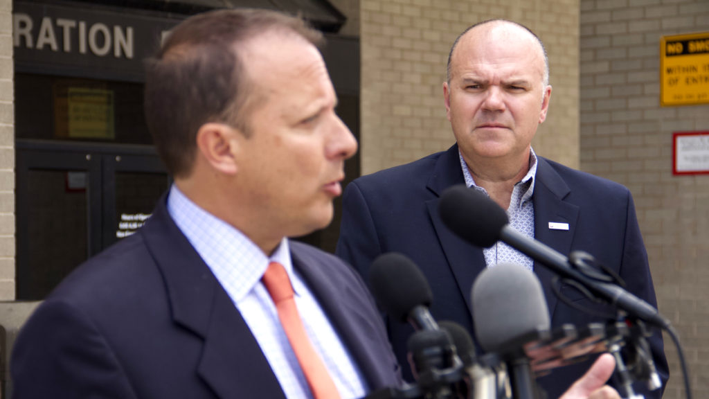 Public Safety Director Troy Riggs (right) looks on while Community Corrections Director Greg Mauro speaks a press conference outside the Police Administration Building on Wednesday, Aug. 21, 2019, in Denver. (Esteban L. Hernandez/Denverite)