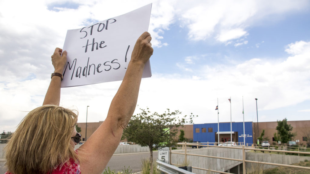 Becky Keiter holds a sign outside of the GEO private immigrant detention facility in Aurora as protesters spoke out against child separations in immigration cases, June 14, 2018. (Kevin J. Beaty/Denverite)
