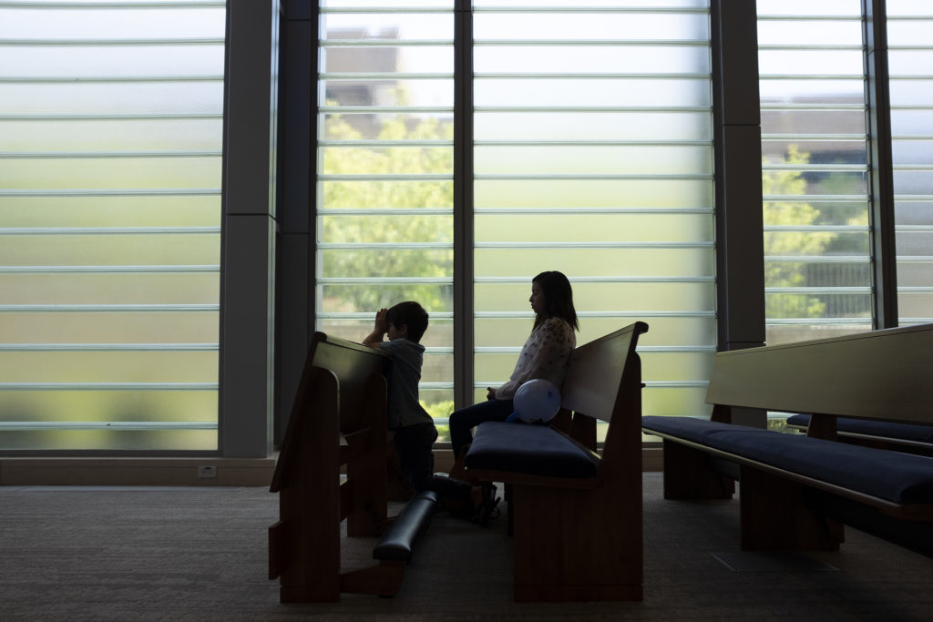 Laura Peniche prays next to her son, Leonardo, inside a chapel at St. Joseph Hospital. It's a regular stop during her visits to see her father. July 18, 2019. (Kevin J. Beaty/Denverite)