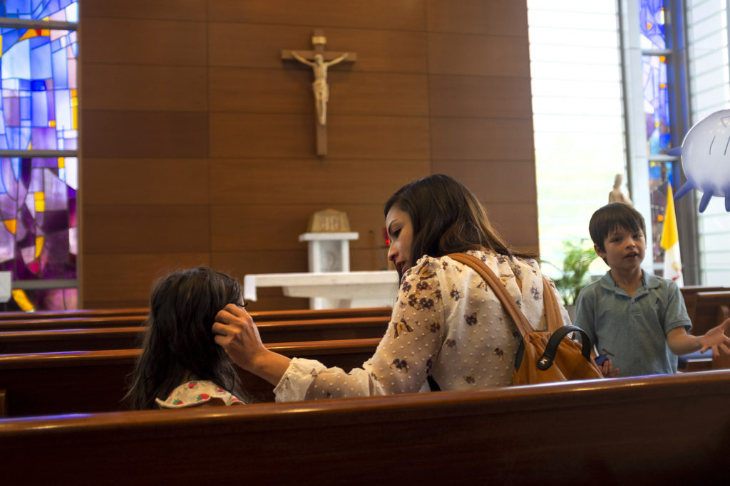 Laura Peniche strokes her daughter Athena's hair inside a chapel at St. Joseph Hospital, a regular stop during her visits to see her father. July 18, 2019. (Kevin J. Beaty/Denverite)