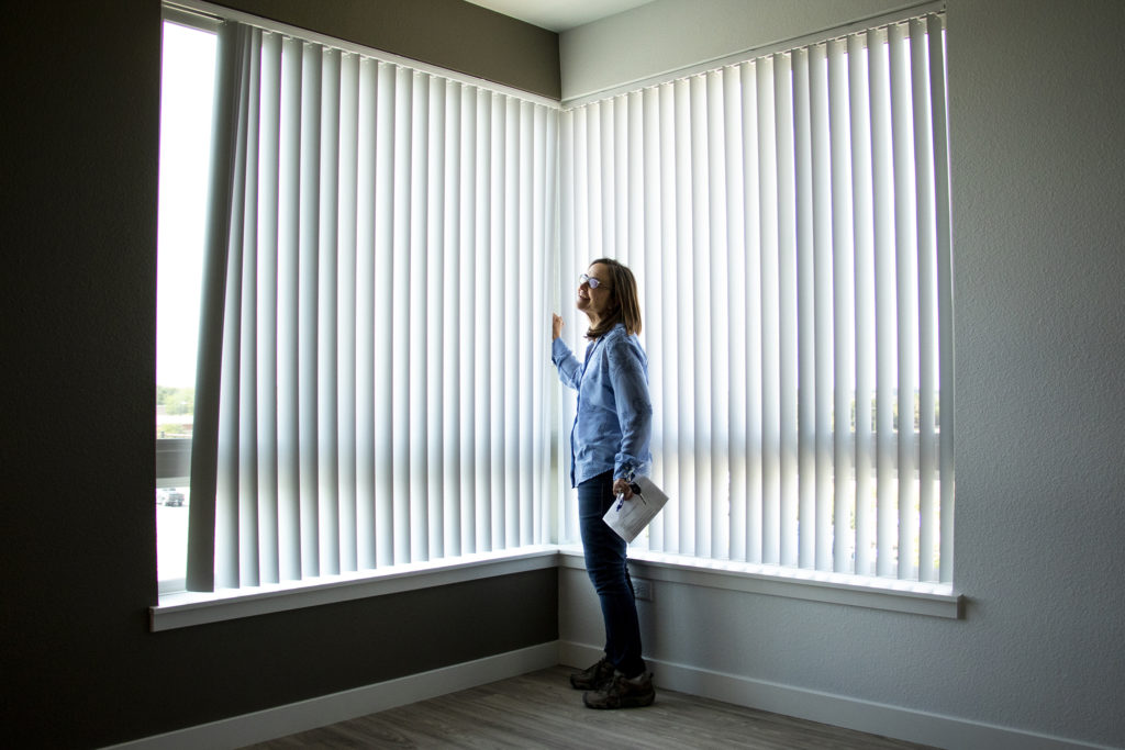 Sarah Vogl, director of housing development with Unison Housing Partners, opens the blinds inside a two-bedroom apartment at Crossing Pointe North in Thornton, Sept. 3, 2019. (Kevin J. Beaty/Denverite)