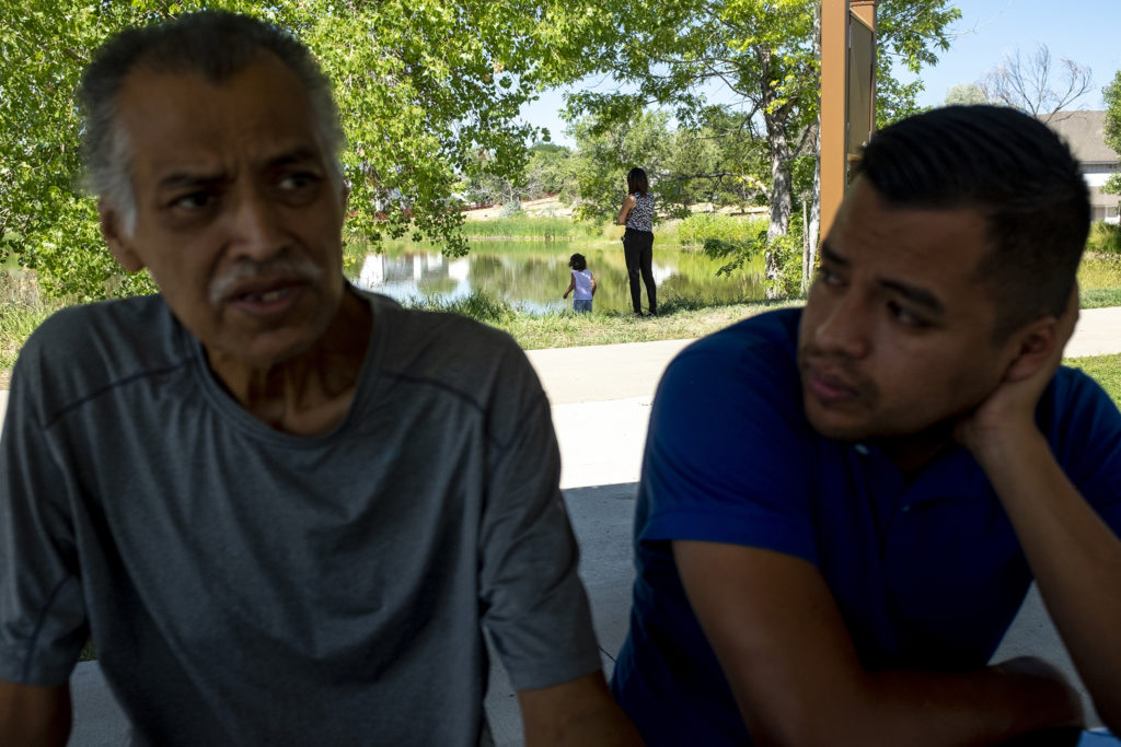 Armando Peniche-Cruz and his son, Armando Jr., talk as his daughter, Laura, watches his granddaughter, Athena, play by a pond. Aug. 15, 2019. (Kevin J. Beaty/Denverite)