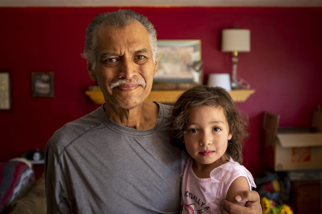 Armando Peniche-Cruz poses for a portrait with his granddaughter, Athena, inside his son's home. Aug. 15, 2019. (Kevin J. Beaty/Denverite)