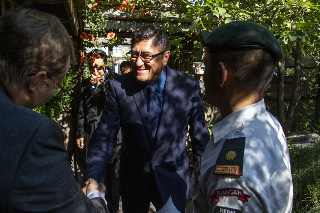 Major General Shashi CB Singh of Nepal's army is greeted as he enters the garden behind the Domo Japanese Country Food Restaurant, Aug. 31, 2019. (Kevin J. Beaty/Denverite)