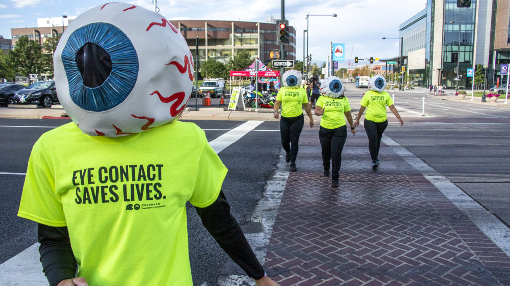 Katie Clements, a CDOT eyeball, crosses Speer Boulevard to promote eye contact awareness, Sept. 4, 2019. (Kevin J. Beaty/Denverite)