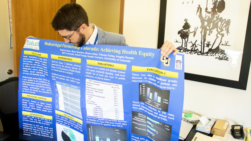 Attorney Marc Scanlon, with Medical Legal Partnership Colorado, shows a poster presentation inside his office at the Salud Family Medical Center in Commerce City, Sept. 10, 2019. (Kevin J. Beaty/Denverite)