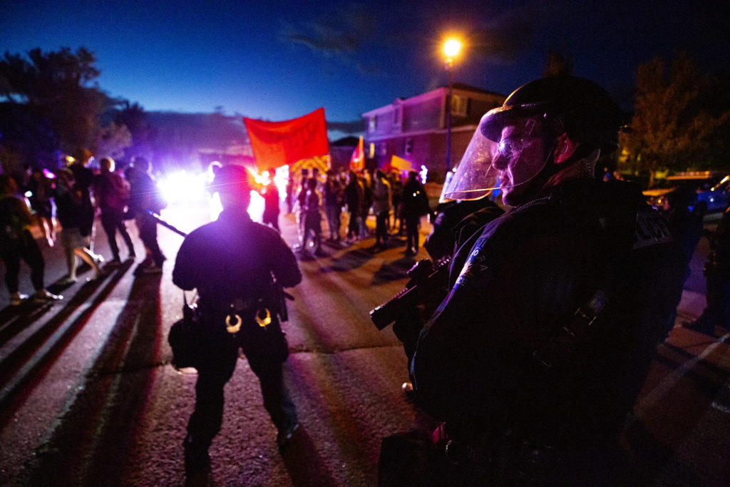 Aurora Police officers make a line in the street as immigration activists march on the home of Johnny Choate, GEO Group's lead of their contract immigration jail in Aurora. Sept. 19, 2019. (Kevin J. Beaty/Denverite)