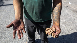 Alex Mendoza, who works at a body shop off Brighton Boulevard, shows off his hands after a day of work. Sept. 24, 2019. (Kevin J. Beaty/Denverite)