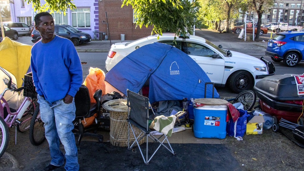 Kennith Body stands near his tent as Denver Police officers tell people living in the encampment near Sonny Lawson Park that they need to leave. Sept. 26, 2019. (Kevin J. Beaty/Denverite)