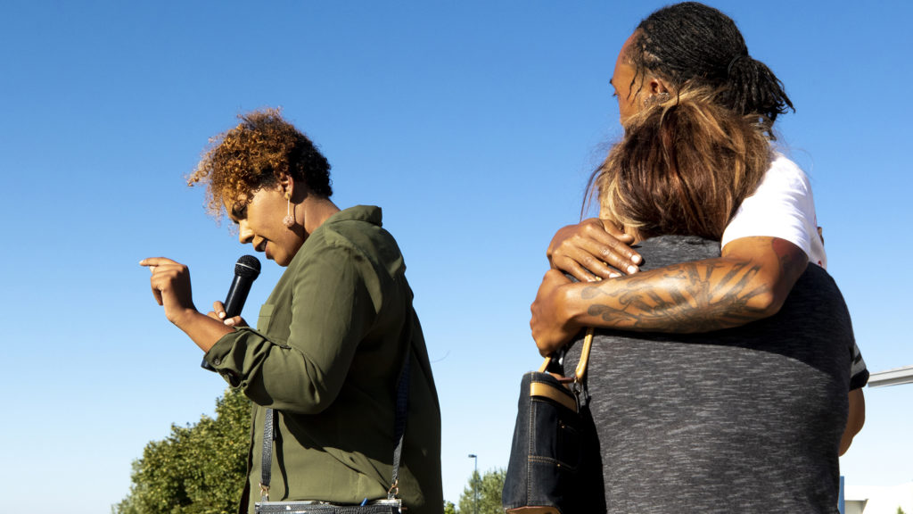 Autumn Lawrence, Aiden Lawrence's mother, speaks to a crowd gathered outside of the Green Valley Ranch Recreation Center as Joel Hodge embraces Patricia Lopez, the mother of Diego Marquez. Sept. 28, 2019. (Kevin J. Beaty/Denverite)