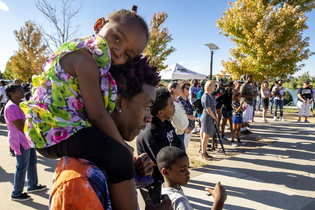 D'vontre Dotson holds his daughter, Majesty, on his shoulders during a gathering to discuss youth gun violence outside of the Green Valley Ranch Recreation Center, Sept. 28, 2019. (Kevin J. Beaty/Denverite)