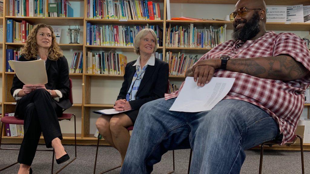 Jason McBride (right) sits next to Denver District Attorney Beth McCann during a press event on Thursday, Sept. 12, 2019, at the Conflict Center in Denver. (Esteban L. Hernandez/Denverite