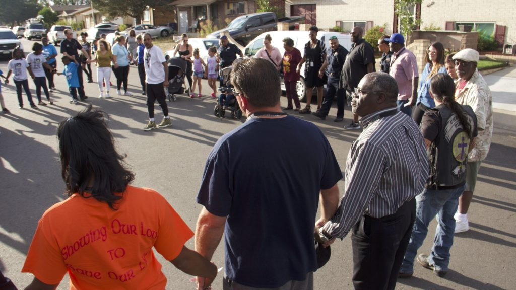 Montbello residents and police hold hands in a prayer circle during a community meeting in Montbello on Wednesday, Sept. 18, 2019, in Denver. (Esteban L. Hernandez/Denverite)