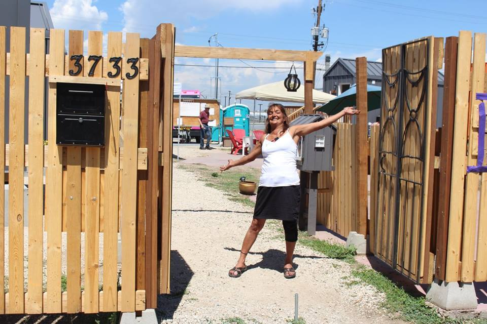 An undated photograph of Rhonda Romero at the front gate of Beloved Community Village shortly after the tiny home community opened in 2017. (Courtesy of Cole Chandler)