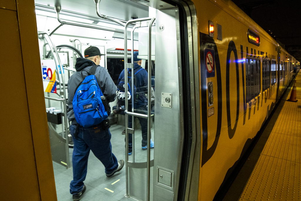 Dominic Ortegon (left) and Shane Romanchuck board a train to work at the 38th and Blake RTD station, Oct. 1, 2019. (Kevin J. Beaty/Denverite)