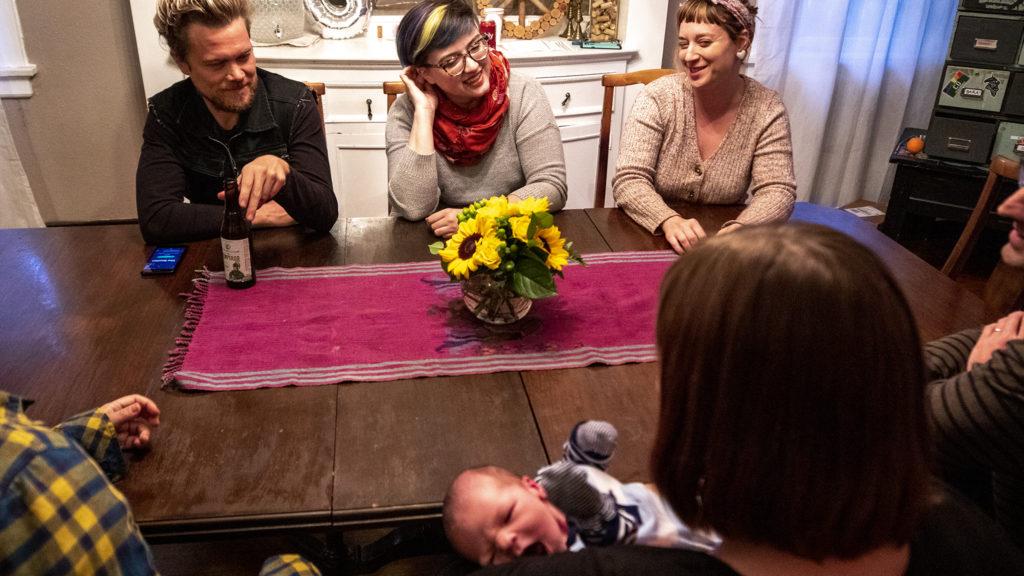 Josiah Hesse (clockwise from top-left), Samantha Hinshaw, Meredith Turk, Stephen Polk, Sarah Wells, baby Charlie Wells-Polk and Sara Baumann sit around their communal table at 901 N. Clarkson St. Oct. 1, 2019. (Kevin J. Beaty/Denverite)