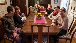 Stephen Polk (left to right), Sarah Wells and baby Charlie Wells-Polk, Sara Baumann, Paul Bindel, Josiah Hesse, Samantha Hinshaw and Meredith Turk sit around the table in Capitol Hill, Oct. 1, 2019. (Kevin J. Beaty/Denverite)