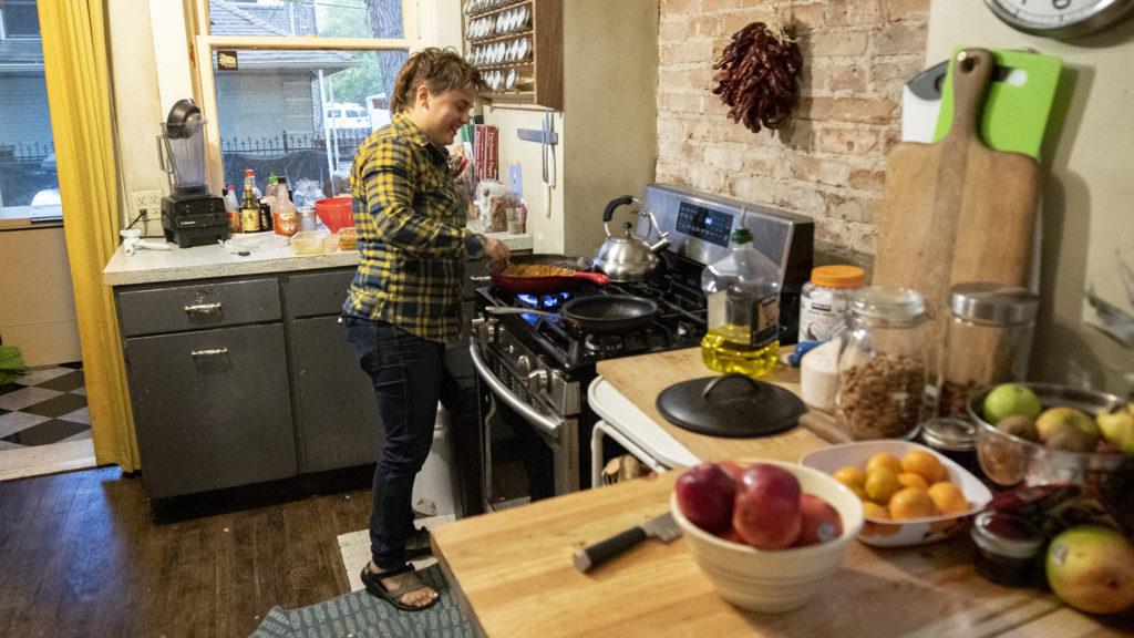 Sara Baumann cooks inside her shared home at 901 N. Clarkson St. Oct. 1, 2019. (Kevin J. Beaty/Denverite)