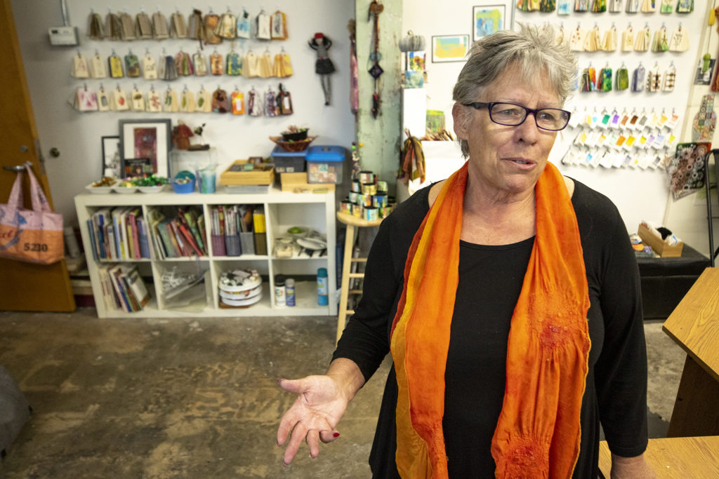 Mixed-media artist Carol Waugh speaks to a reporter inside inside her studio at the Dry Ice Factory on Walnut Street, Five Points. Oct. 2, 2019. (Kevin J. Beaty/Denverite)