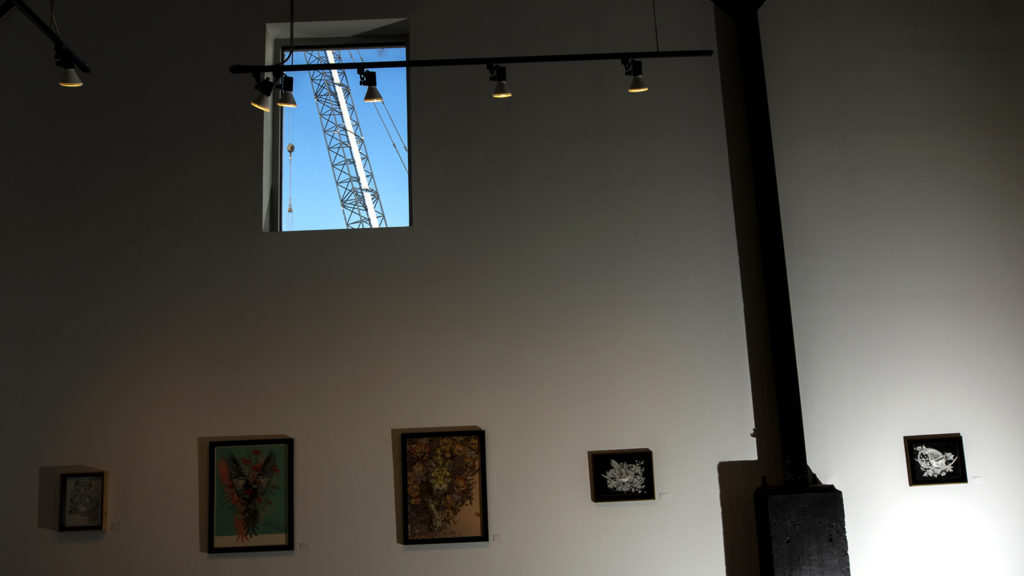 Construction seen through windows at Helikon Gallery and Studios on Wynkoop Street. Five Points, Oct. 2, 2019. (Kevin J. Beaty/Denverite)
