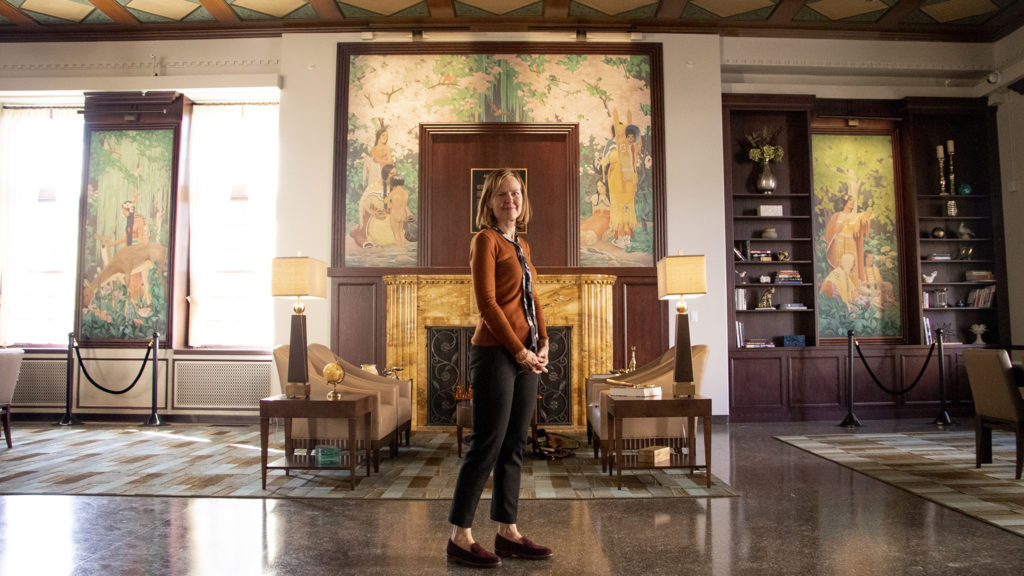 Heidi Huisjen, arts coordinator and curator at Children's Hospital Colorado, poses in front of murals by Allen True inside Tammen Hall, Oct. 15, 2019. (Kevin J. Beaty/Denverite)