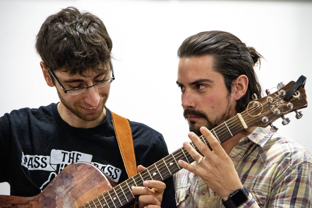 """Gio Darababze (left) and Brodle Kinder, who worked closely with playwright Brenton Weyi on his new piece, """"My Country, My Country,"""" play the same guitar at the same time. Robert and Judi Newman Center for Theater Education at the Denver Center for the Performing Arts, Oct. 16, 2019. (Kevin J. Beaty/Denverite)"""