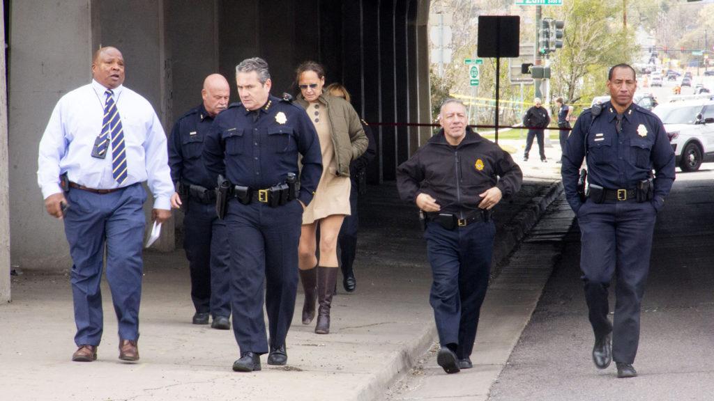 Denver police officials walk a crime scene where a man was fatally shot by an officer on Monday, Oct. 21, in the Lincoln Park neighborhood. (Esteban L. Hernandez/Denverite)