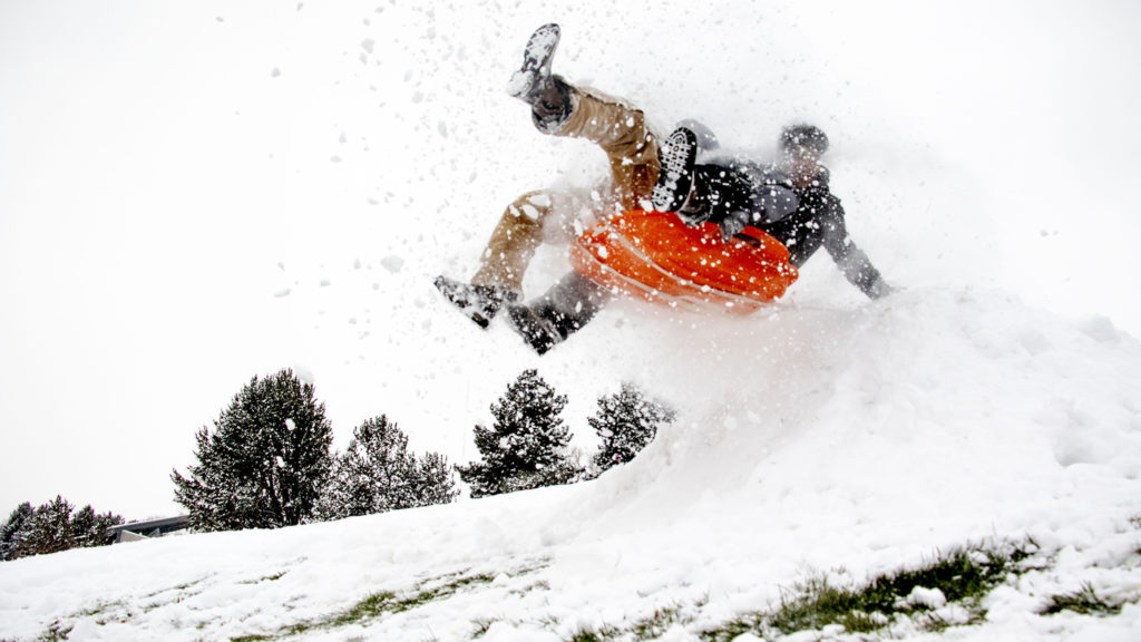 Cruz Ortega and Aryel Ramos fly over a jump at Ruby Hill Park on small sled on a snow day, Oct. 29, 2019. (Kevin J. Beaty/Denverite)