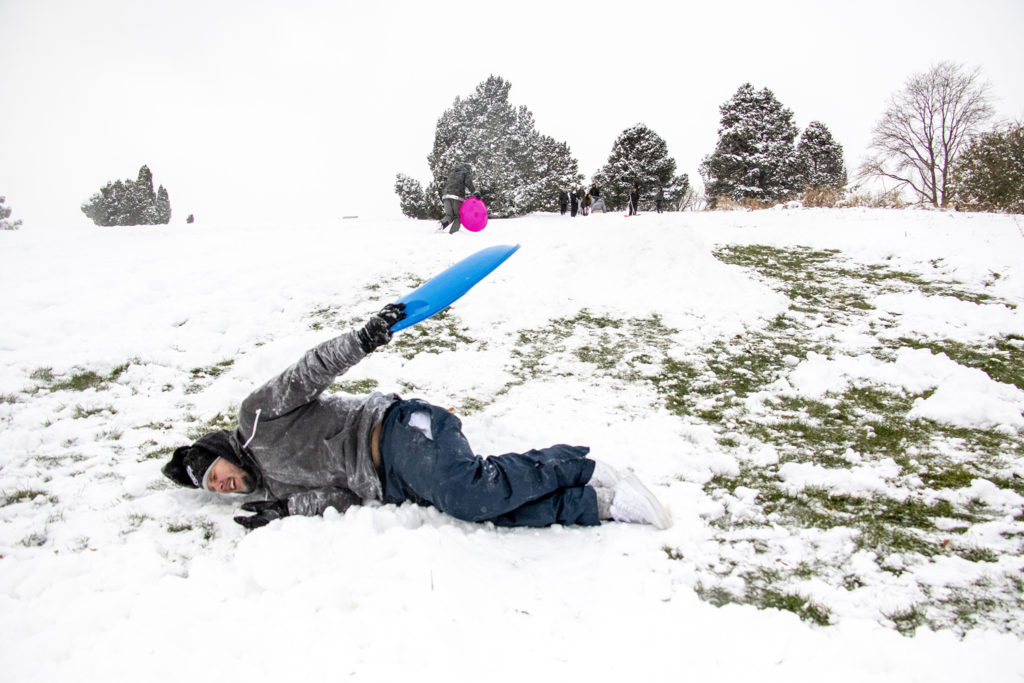 Martin Lomeli deals with the effects of hitting a big jump with a small sled at Ruby Hill Park on a snow day, Oct. 29, 2019. (Kevin J. Beaty/Denverite)