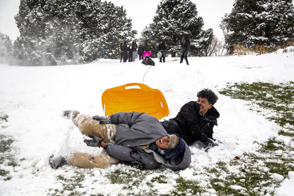 Cruz Ortega and Aryel Ramos stagger from a hard landing from a jump in Ruby Hill Park on a snowy day on October 29, 2019. (Kevin J. Beaty / Denverite)