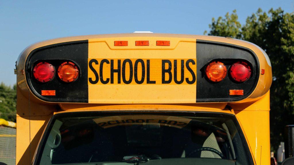 A school bus sits outside Alameda International Senior/Junior High School in Lakewood. (Kevin J. Beaty/Denverite)