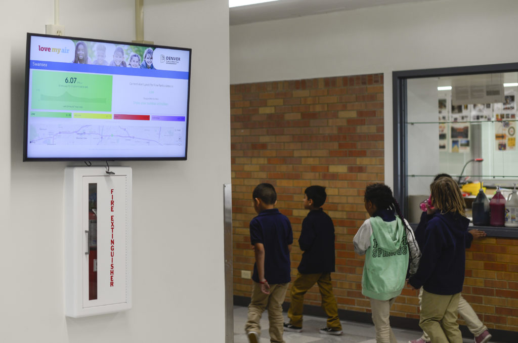 Children walk past a screen displaying air quality information at Swansea Elementary School on Oct. 17, 2019. (Lindsay Fendt