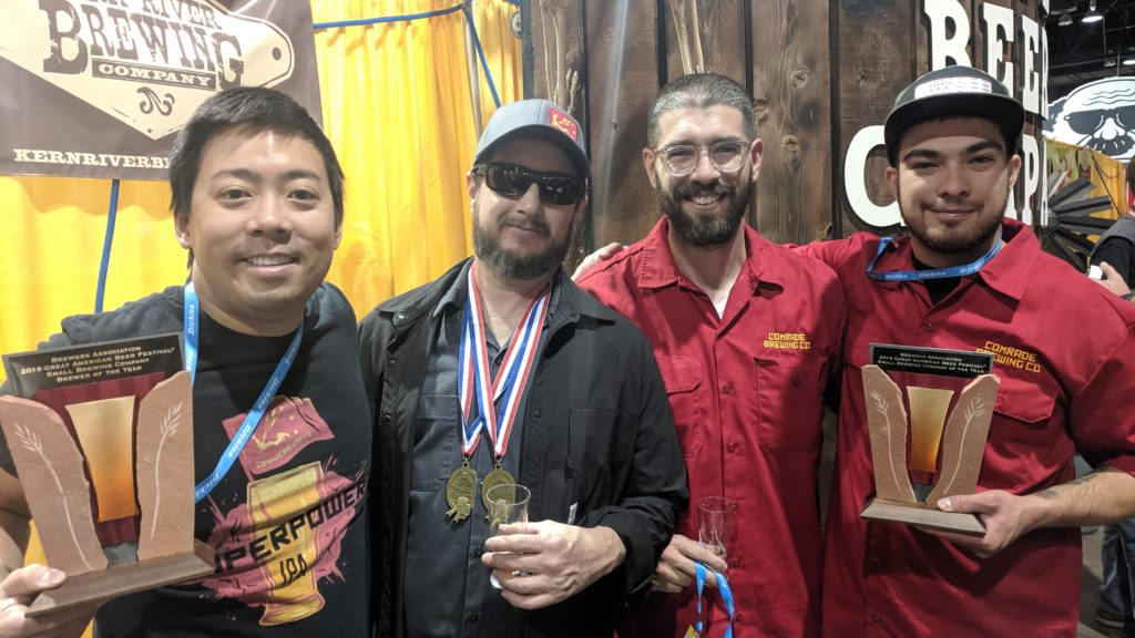 From left: owner David Lin, head brewer Marks Lanham, Jake Lancaster and Rio Urioste of Comrade Breweing Co. team pose with their awards at Great American Beer Festival. Oct. 5, 2019. (Eric Gorski for Denverite)