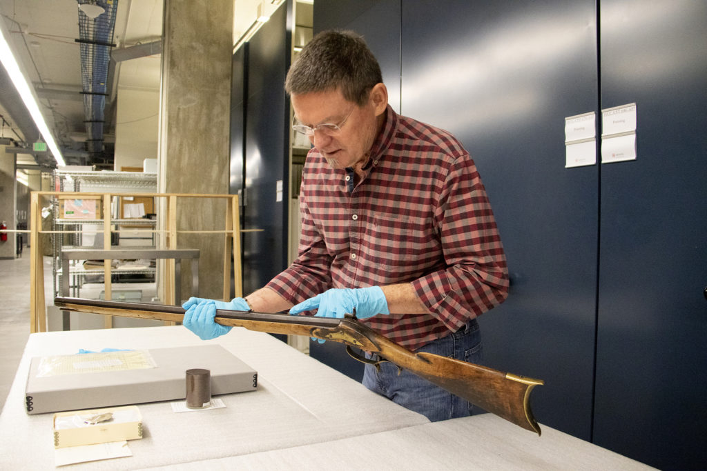 """History Colorado curator James Peterson shows a reporter """"Noisy"""" Tom Pollack's deadly long rifle inside the museum's archive space downtown, Oct. 15, 2019. (Kevin J. Beaty/Denverite)"""