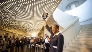 """Denver Deputy Mayor Allegra """"Happy"""" Haynes ceremoniously removes her hard hat as Denver Art Museum officials celebrate the end of their new Martin Building's construction phase and the start of their """"museum making"""" stage. Nov 13, 2019. (Kevin J. Beaty/Denverite)"""